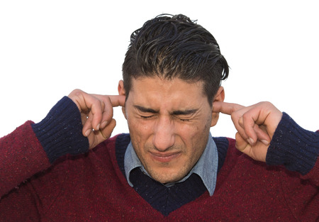 deafening: A man putting his fingers in his ears to shield himself from loud noise or some other painfull event Stock Photo