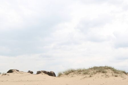 room for text: Cloudy sky above a dune rim with room for text