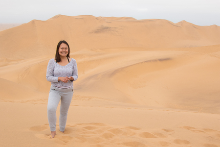 Indonesian girl posing on Dune 7 in Walvis Bay, Namibia Stock Photo
