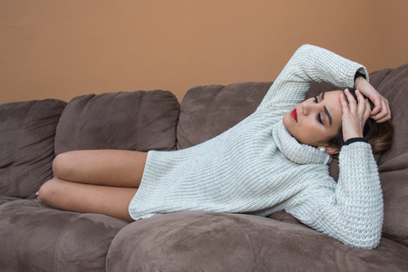 Pretty brunette lying worried on the sofa Stock Photo