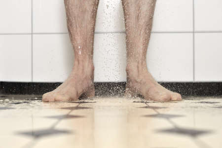 showering: showering, taken with a central composition, a small depth of field, focus is on toes and falling water drops