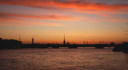 The White Nights of Petersburg. The silhouettes of Peter-and-Pauls Cathedral against the sunrise and the Neva River. photo
