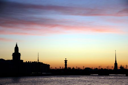 White nights. View of the Neva river and silhouettes of Curiosity Chamber and Peter and Paul Fortress against the sunrise. St.Petersburg, Russia. photo