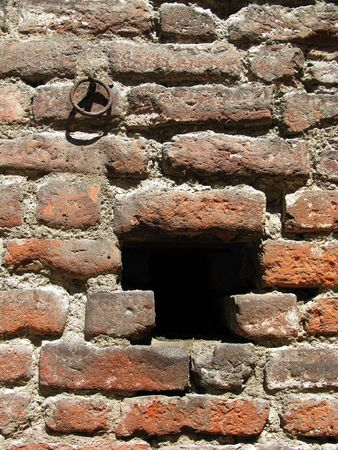 revetment: An old Roman brick wall of the Milano castle with a hole in it.
