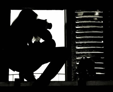 A silhouette of the professional girl-grapher taking pictures from the attic window photo
