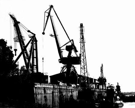 Silhouettes of Portal Cranes in a Harbor Stock Photo
