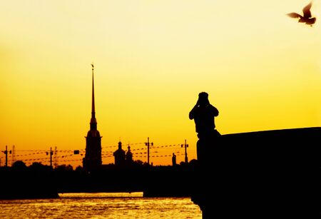 siluet: The White Nights of Petersburg. The silhouette  of the photographer taking pictures of Peter-and-Pauls Cathedral against the sunrise and the Neva River. Focus on the man.