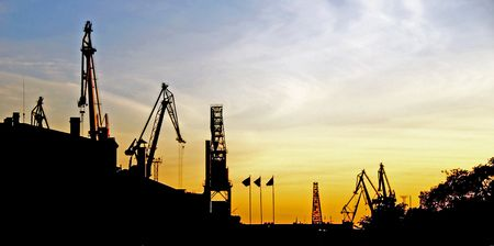 Silhouette of portal cranes in harbor, shot during sunset