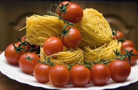 Fresh Tomato and spaghetti on the white plate.