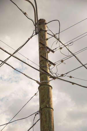 Traditional above ground high voltage pole with lots of wires against cloudy sky photo