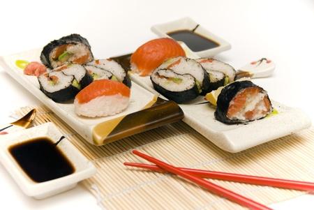 Sushi with chopsticks against white background.  Stock Photo