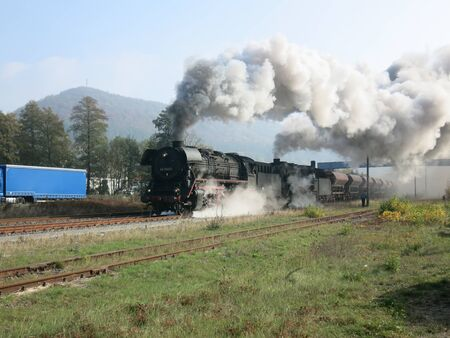 Two steam locomotives in front of freight train leave Stockfoto