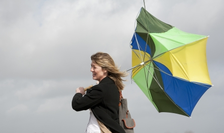 Woman struggles onto her inside out umbrella