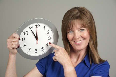 Woman with surprised expression holding a clock photo