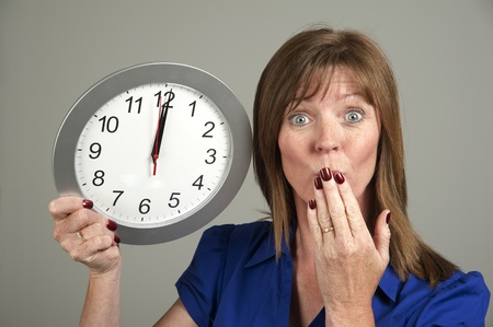 ticking away: Woman with surprised expression holding a clock