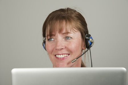 an operative: Woman using a headset and computer