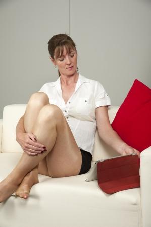 falda corta: La mujer llevaba minifalda sentada en un sof�