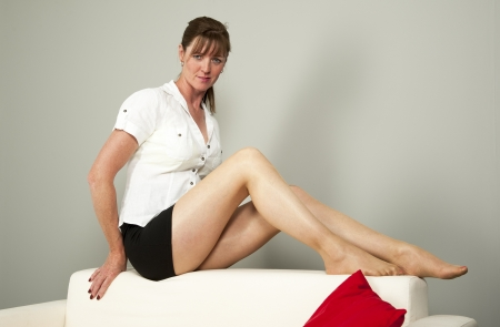 leggy: Woman sitting on the back of a white settee