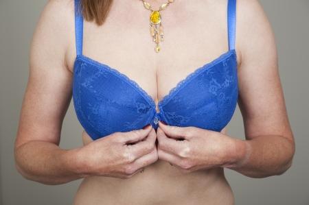 fastens: Woman fastens her front fastening bra