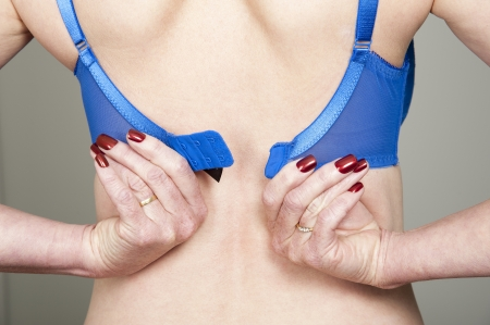 fastens: Woman fastening her bra Stock Photo