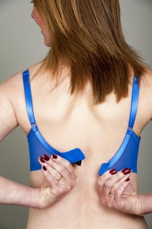 undoing: Woman fastening her bra Stock Photo