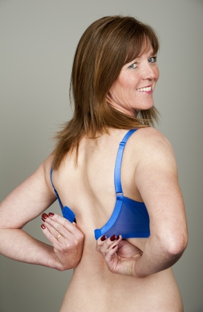 Woman fastening her bra Stock Photo