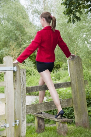 stile: Woman stepping over a stile