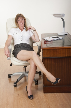 Secretary showing a leggy pose sitting at a desk