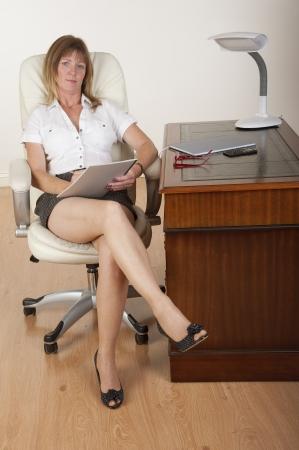 busty: Secretaresse maken van aantekeningen, zittend op een bureau