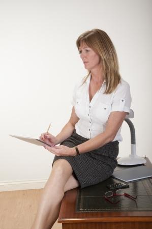 secretarial: Secretary taking notes sitting on a desk