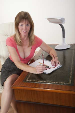 Mid aged secretary sitting at her desk photo