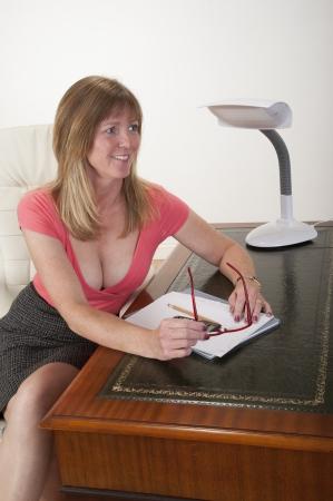 busty: Mediados secretaria de mediana edad sentado en su escritorio Foto de archivo