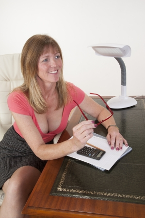 low blouse: Mid aged secretary sitting at her desk Stock Photo