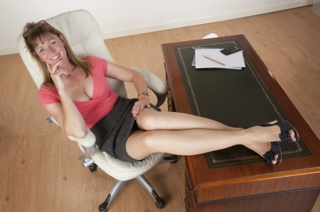 low cut: Mid aged secretary sitting at her desk Stock Photo