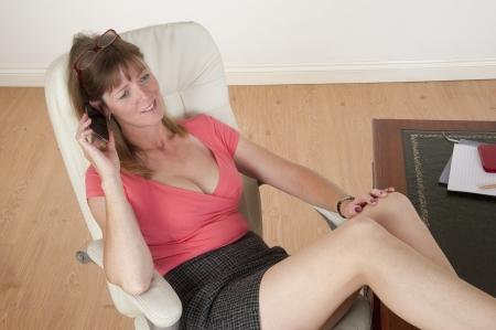 secretarial: Mid aged secretary sitting at her desk Stock Photo