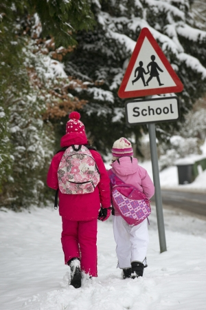 Children walking to school along a snow covered road Stock Photo