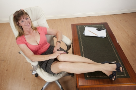 Woman sitting on a chair with her feet on the desk photo