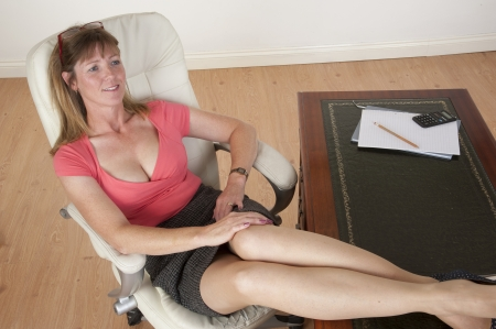 low blouse: Woman sitting on a chair with her feet on the desk