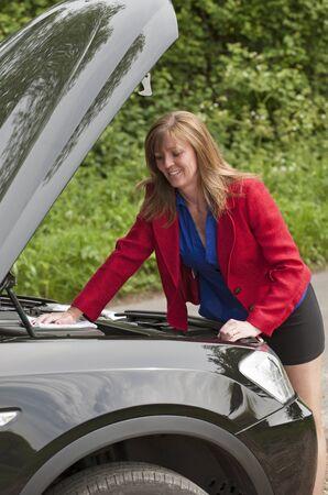 bonnet up: Female motorist with the car bonnet up