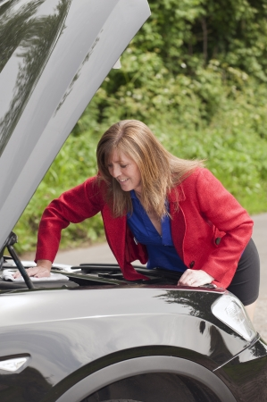 bonnet up: Female motorist with the car bonnet up