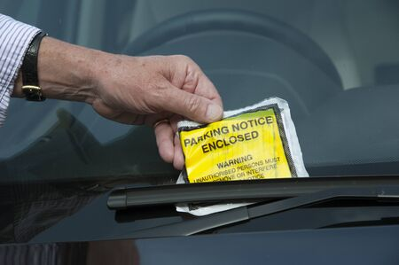 Man removing parking ticket from windscreen Stock fotó