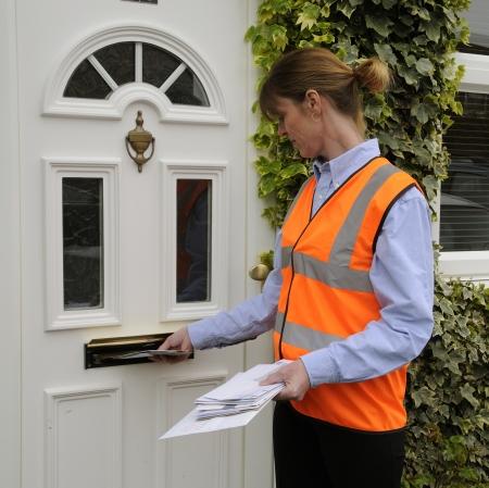 Postwoman delivering letters at a front door