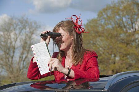 Female race goer using binoculars