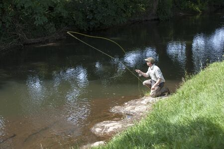 Man fly fishing on River Lyd Devon UK photo