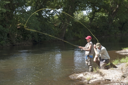 Fly fishing a gillie instructing a pupil River Lyd Devon UK