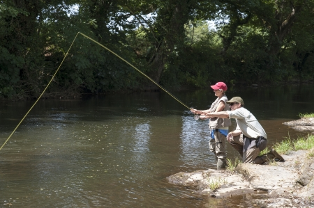 Fly fishing a gillie instructing a pupil River Lyd Devon UK photo