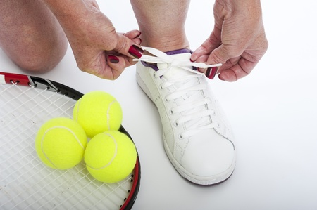 Female tennis player tying shoe lace Stock Photo - 21000185