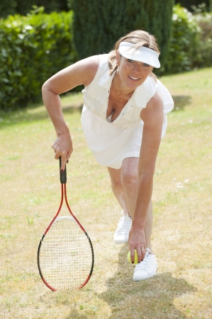 Female tennis player kneeling in seductive pose photo