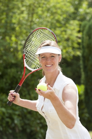 Portrait of a female tennis player holding her racquet and ball Foto de archivo