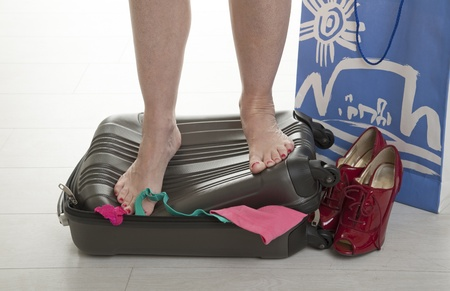 holidaymaker: Female holidaymaker standing on suitcase to force shut
